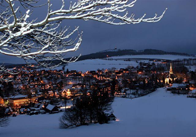 Blick vom winterlichen Schwartenberg auf das beleuchtete Spielzeugdorf Seiffen zur Weihnachtszeit